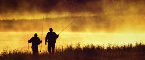 Silhouetted fly fishermen walking on bank of Madison River in Yellowstone National Park
